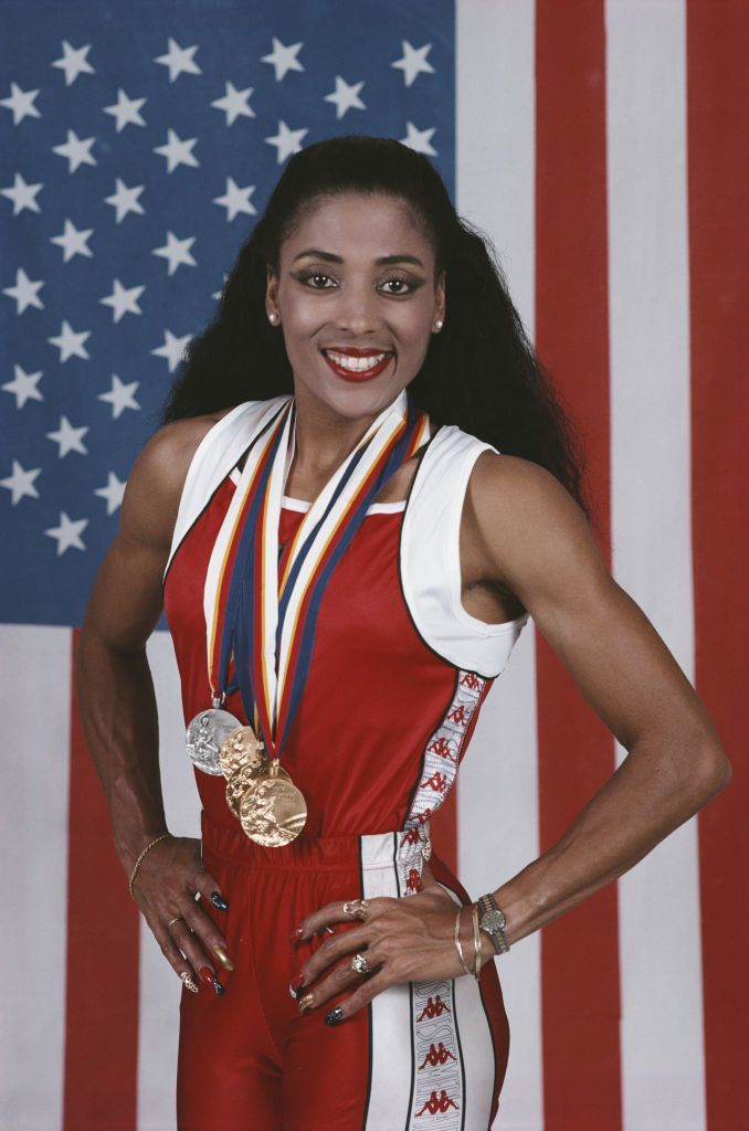 Florence Griffith-Joyner posing in front of the US flag in South Korea on September 25,1988. | Photo: Getty Images