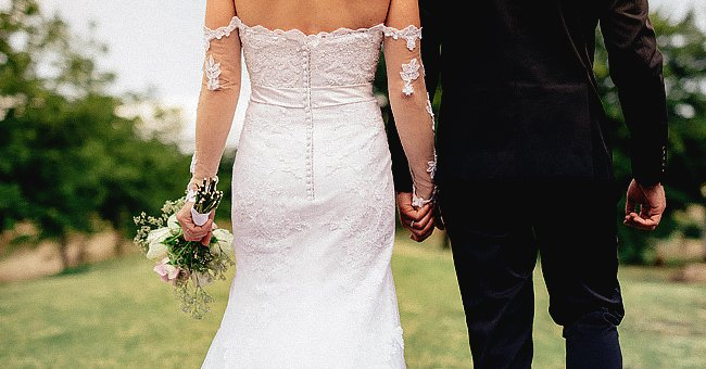 A bride and groom holding hands on their wedding day. | Source: Shutterstock