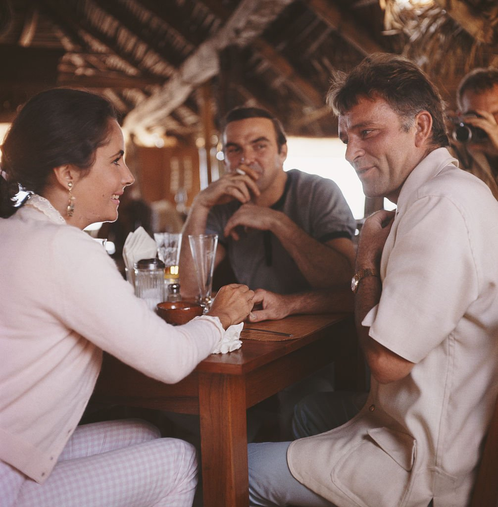 Left to right: actors Elizabeth Taylor (1932 - 2011), Stanley Baker (1928 - 1976) and Richard Burton (1925 - 1984) in a bar, Puerto Vallarta, Mexico, 12th January 1964. Burton is in Mexico for location filming on John Huston's 'The Night Of The Iguana'. | Source: Getty Images