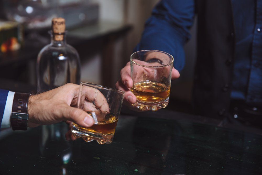 A close-up of two men clinking glasses of whiskey while at bar counter in a pub | Photo: Shutterstock/Romanno