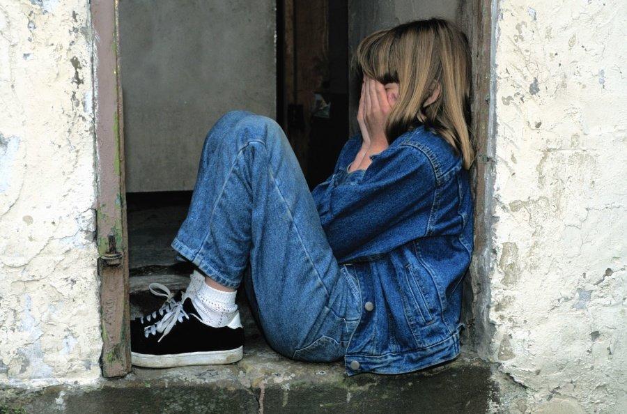 Niña sentada en el suelo llorando con las manos sobre su rostro. | Imagen: Pixnio