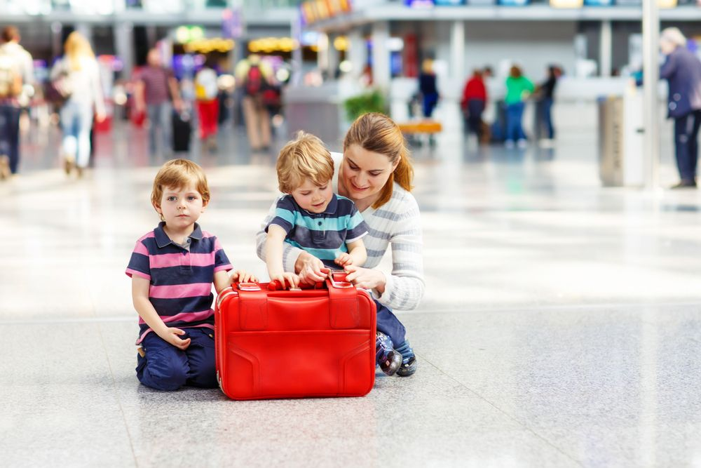 A mother takes care of her kids at the airport. | Source: Shutterstock
