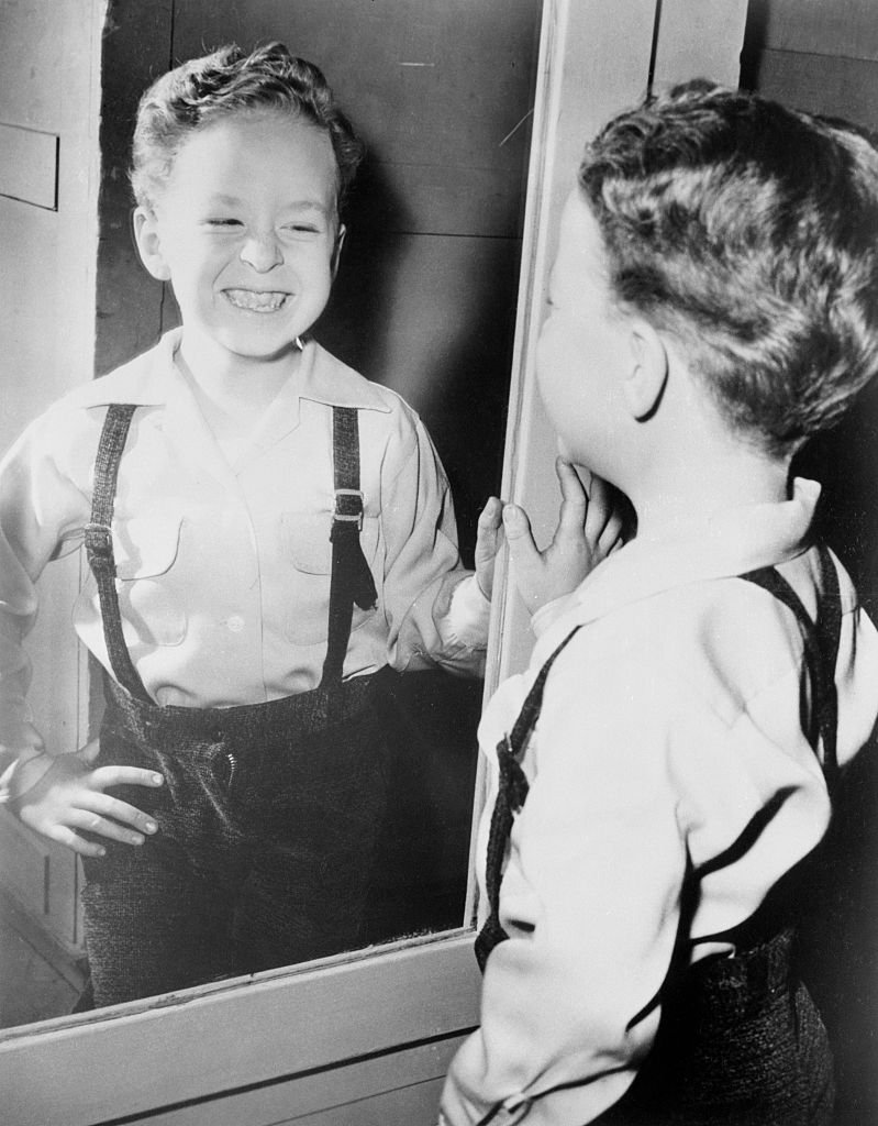 A portrait of Rusty Hamer looking and smiling at his image in a mirror on January 01, 1955   Photo: Getty Images