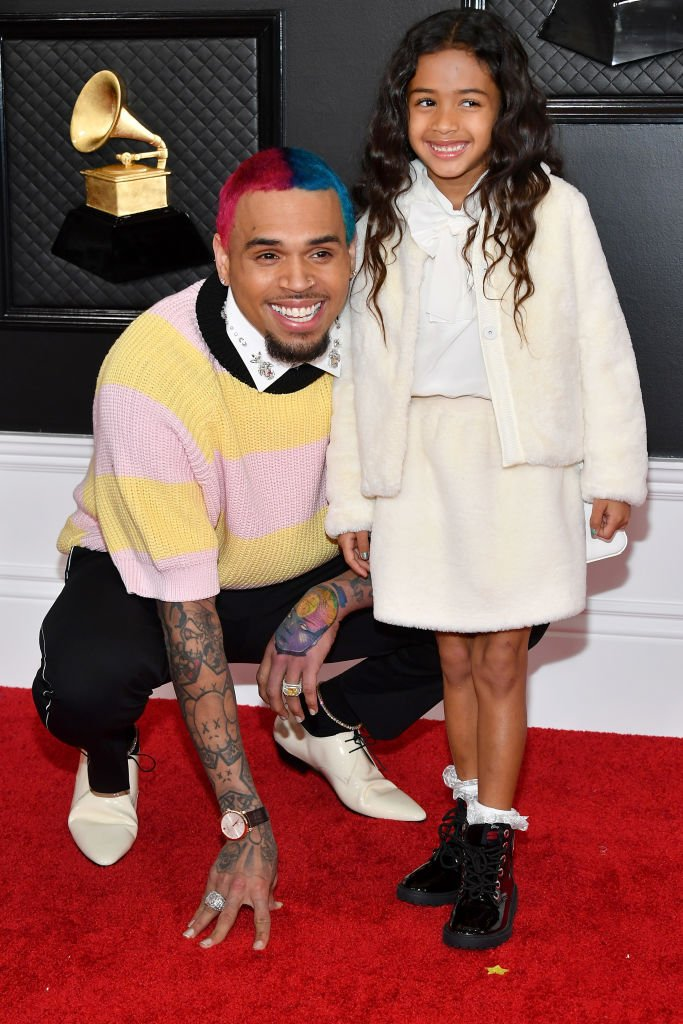 Chris Brown kneels down as he posed with his daughterRoyalty Brown at the 62nd Annual GRAMMY Awards on January 26, 2020, in Los Angeles, California | SourceAmy Sussman/Getty Images