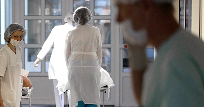 Nurses and doctors wearing face masks can be seen walking through the halls of a hospital | Photo: Shutterstock