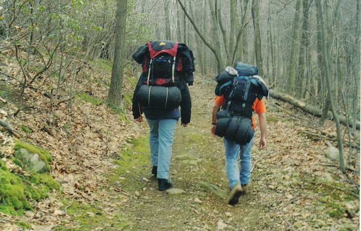 Two guys hiking together in the woods | Photo: Flickr