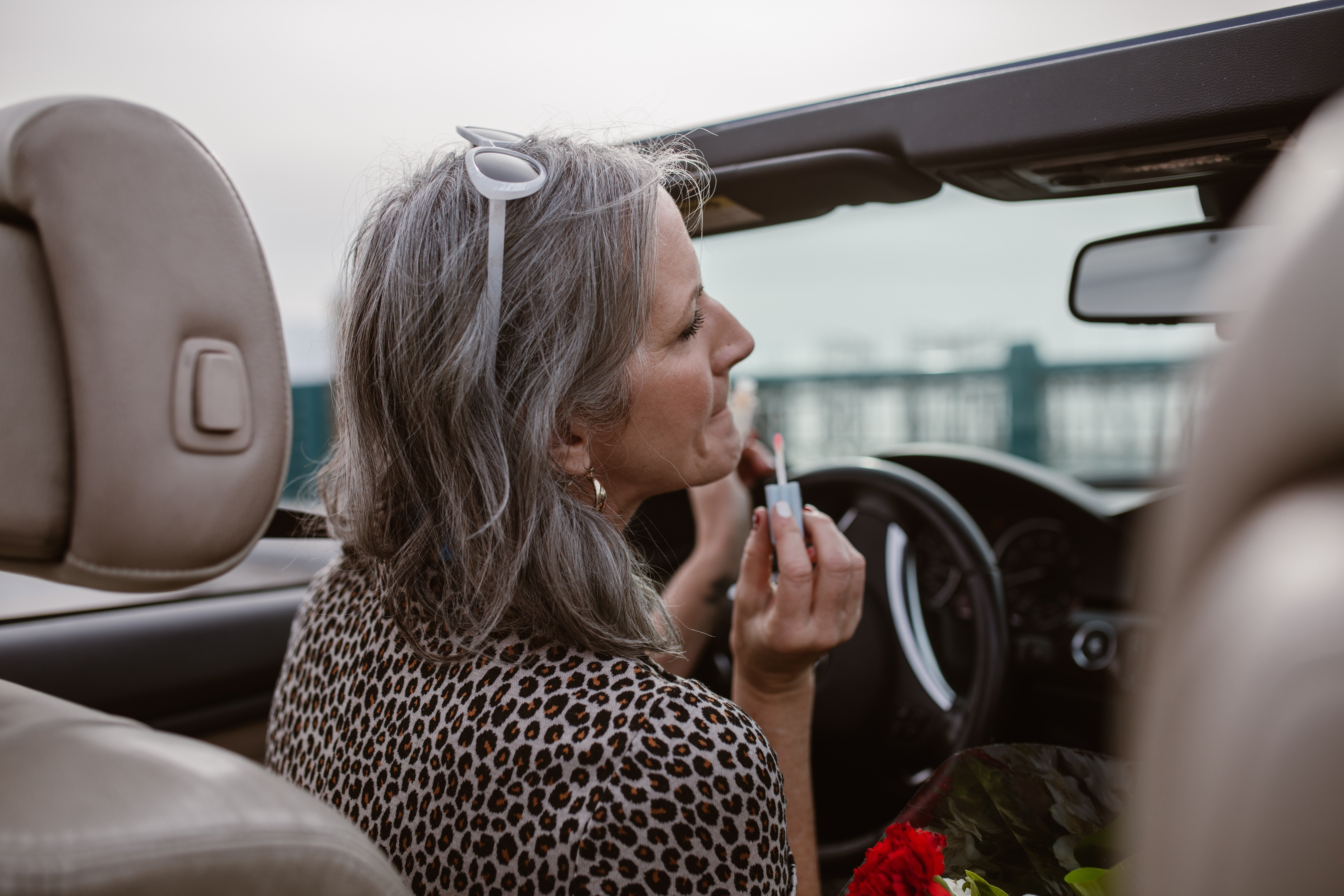 A lady sitting behind the wheel putting lipstick on.   Photo: Pexels