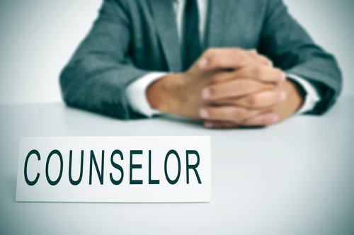 A man with counselor signage on his desk. | Source: Shutterstock.
