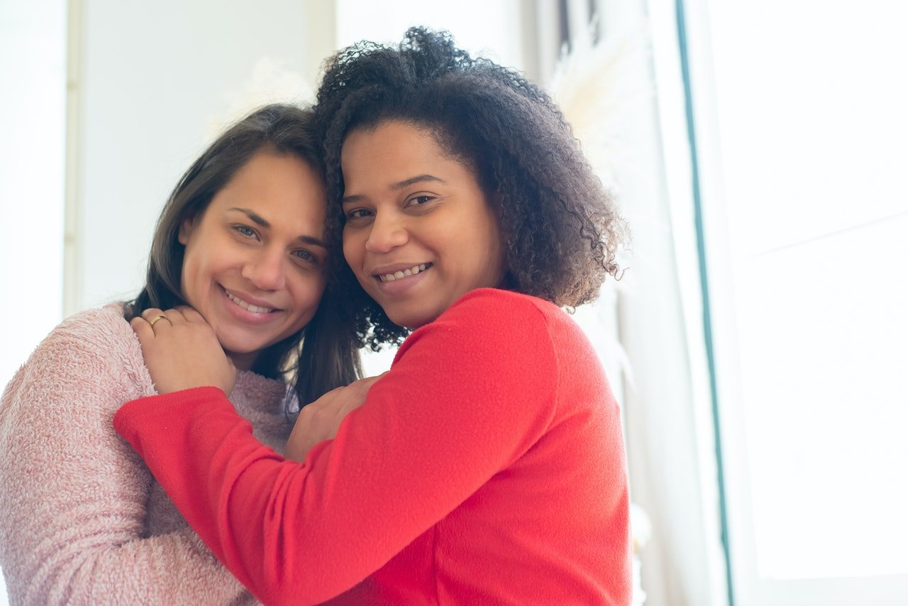 Photo of two women hugging affectionately.   Source: Pexels/Kampus Production