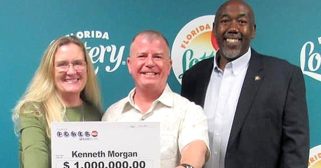 Kenneth Morgan standing in the middle of two individuals while partially holding up a sign showing off lottery winnings of $1 million from the Florida Lottery.   Source: twitter.com/Tuko_co_ke