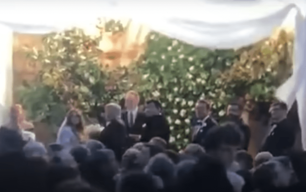 A bride and groom looking back during their wedding. | Source: youtube.com/InsideEdition