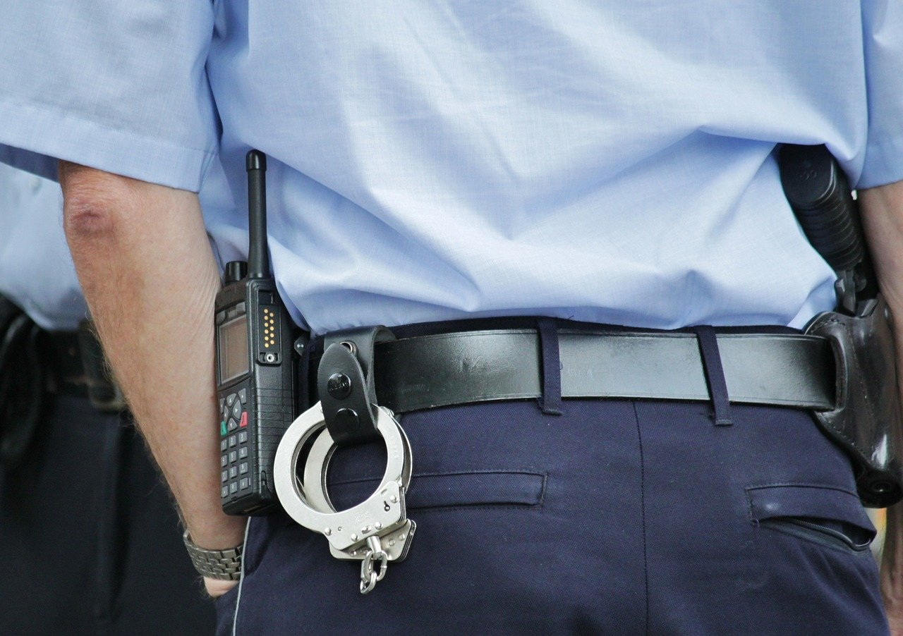 A picture of a police officer's back with a handcuff hanging from his belt. | Photo: Pixabay