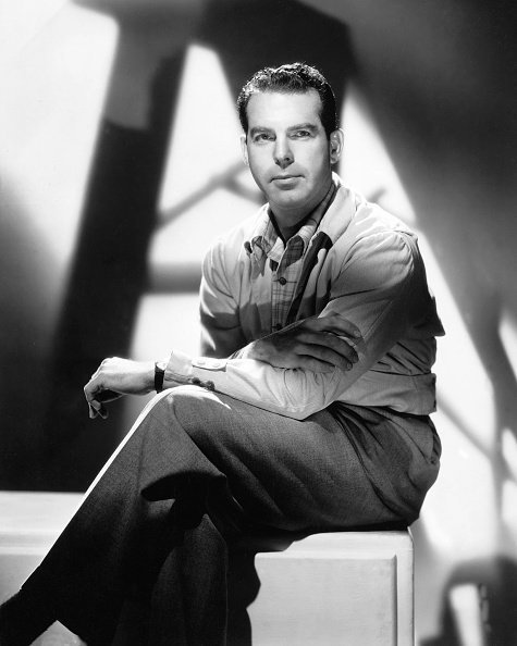 Fred MacMurray (1908-1991), US actor, sitting on a pedestal with his legs crossed, in a studio portrait, against background of shadows, circa 1950 | Photo: Getty Images