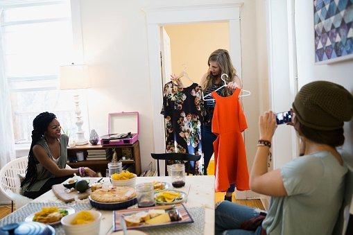 Femme montrant ses choix vestimentaires à ses amis | Photo : Getty Images