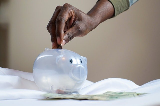 Person putting the coin in a piggy bank |  Photo: Pexels