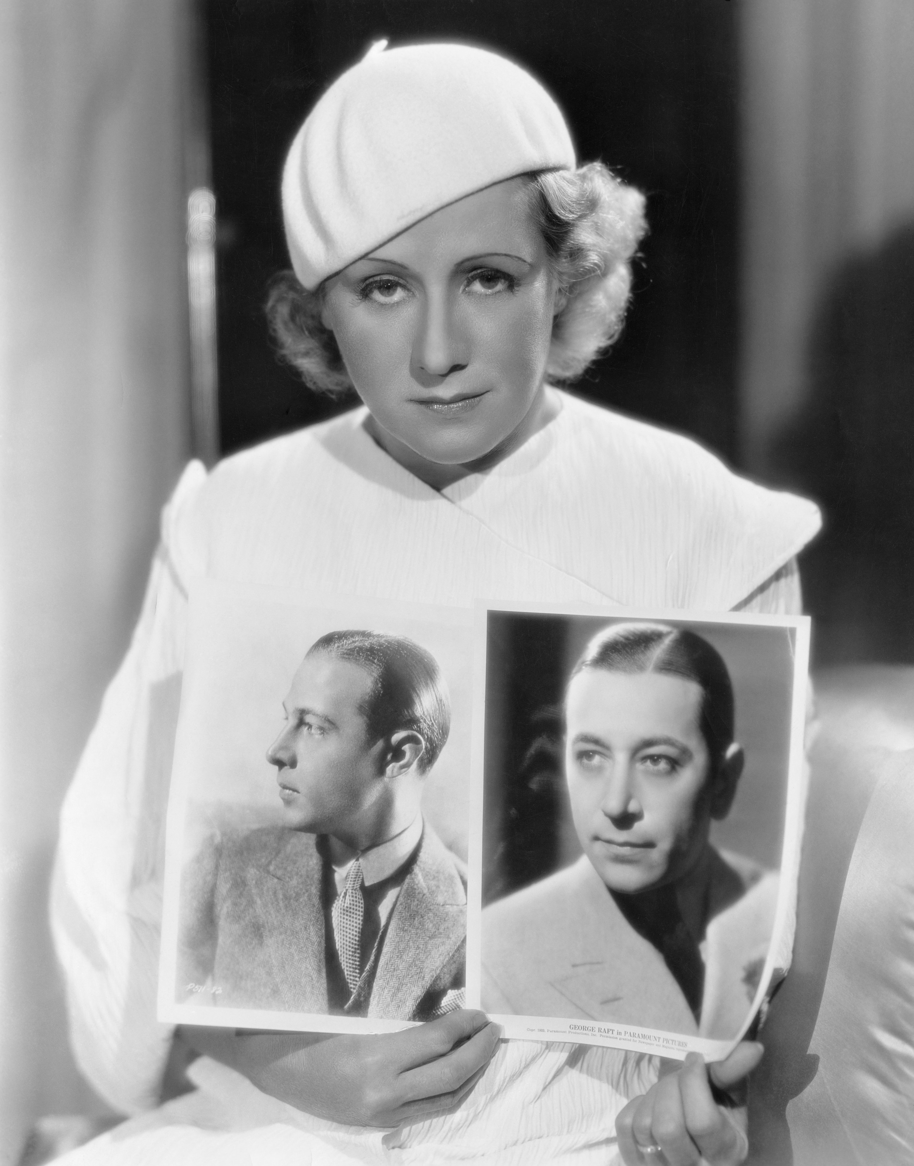 Jean Acker held up photos of her late ex-husband Rudolph Valentino and George Raft for comparison on 01 January, 1933 | Photo: Getty Images