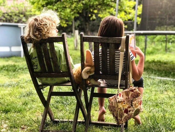 Deux enfants assissent sur une chaise entrain de lire un livre | Photo : Unsplash