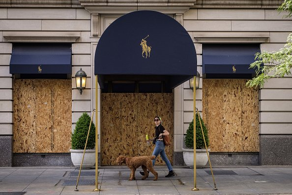 A pedestrian walks a dog past a Ralph Lauren store on Michigan Avenue in Chicago, Illinois on Friday, June 5, 2020. | Photo: Getty Images