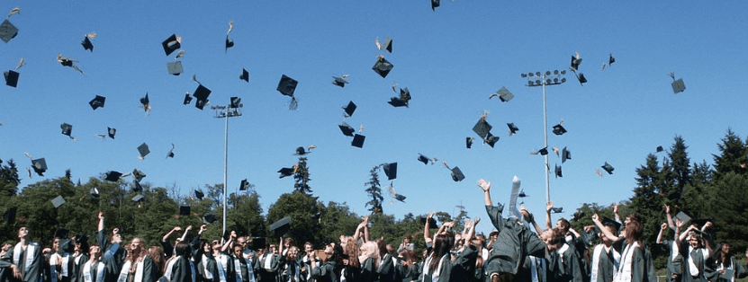 A photo of graduates with their caps thrown in the air in celebration | Source: Pixabay