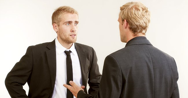 A man in a suit looks concerned while talking to another man. | Photo: Getty Images