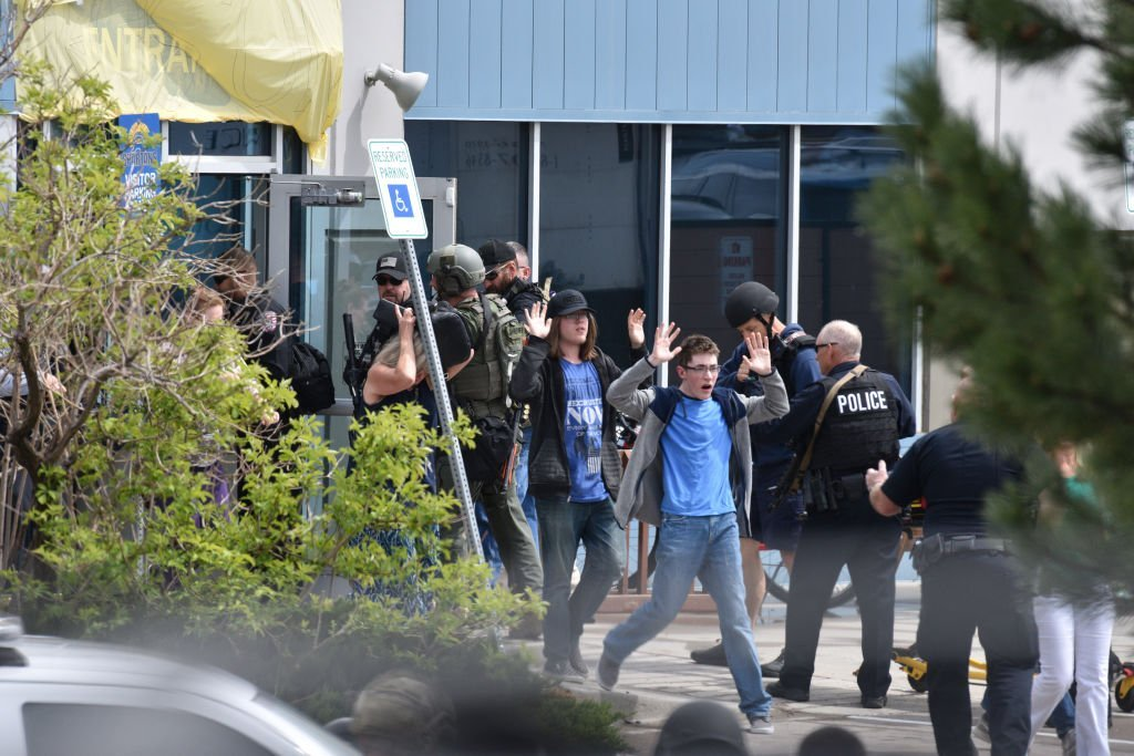 Students and teachers raise their arms as the exit the scene of a shooting at the STEM School Highlands Ranch on May 7, 2019. Photo: Getty Images/Global Images Ukraine