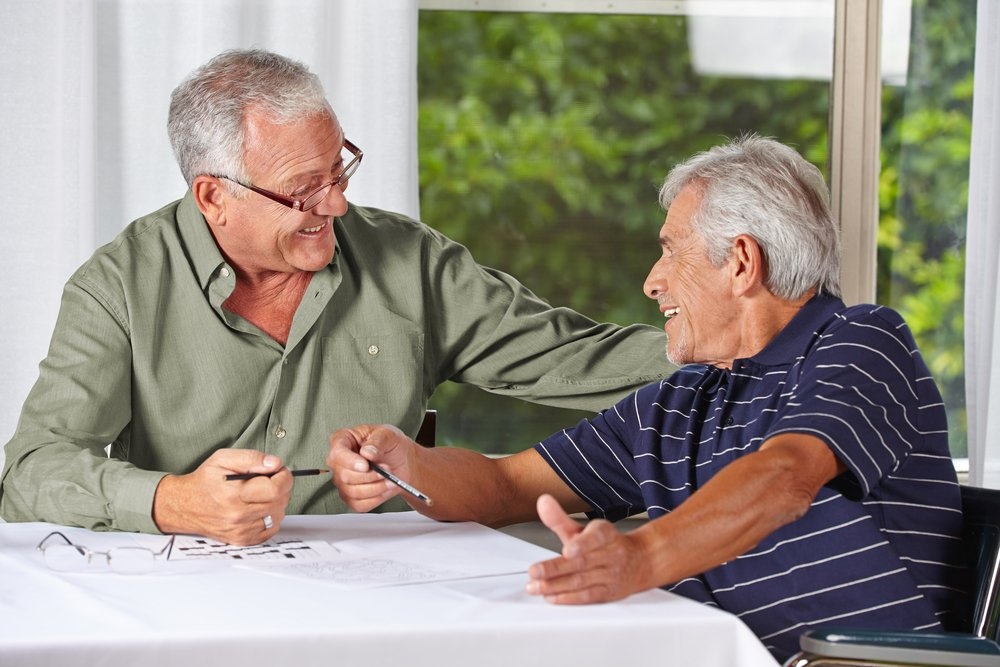 Two happy senior men solving crossword puzzle. | Photo: Shutterstock.