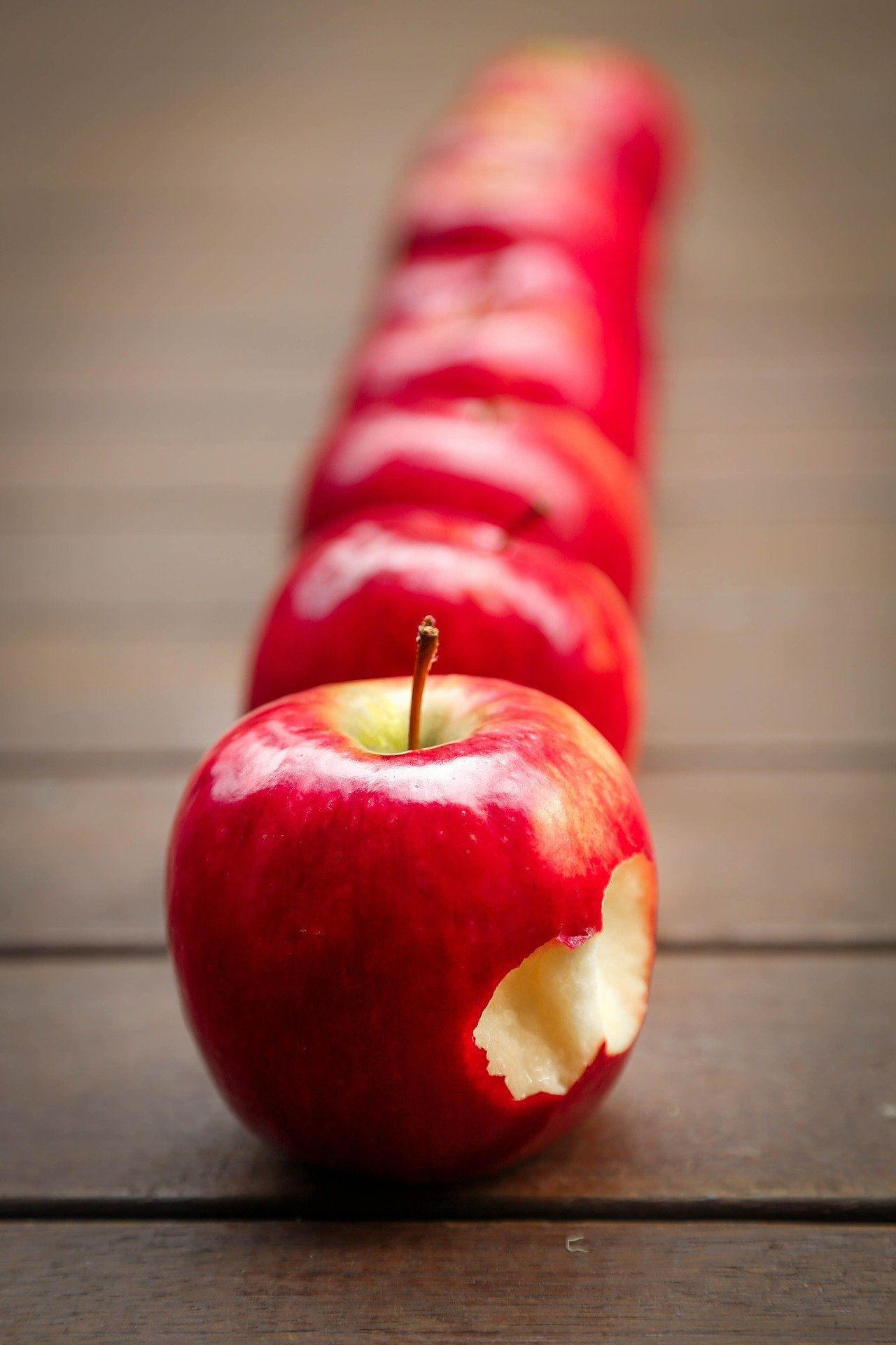 Apples placed on a table in a straight line with the first one featuring bite marks   Photo: Pixabay/Tracy Lundgren