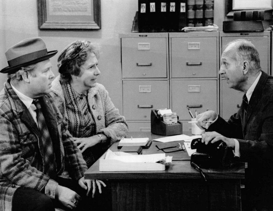 Publicity photo of Carroll O'Connor and Jean Stapleton as Archie and Edith Bunker and guest star James O'Reare as the government official in 1973. | Source: Wikimedia Commons.