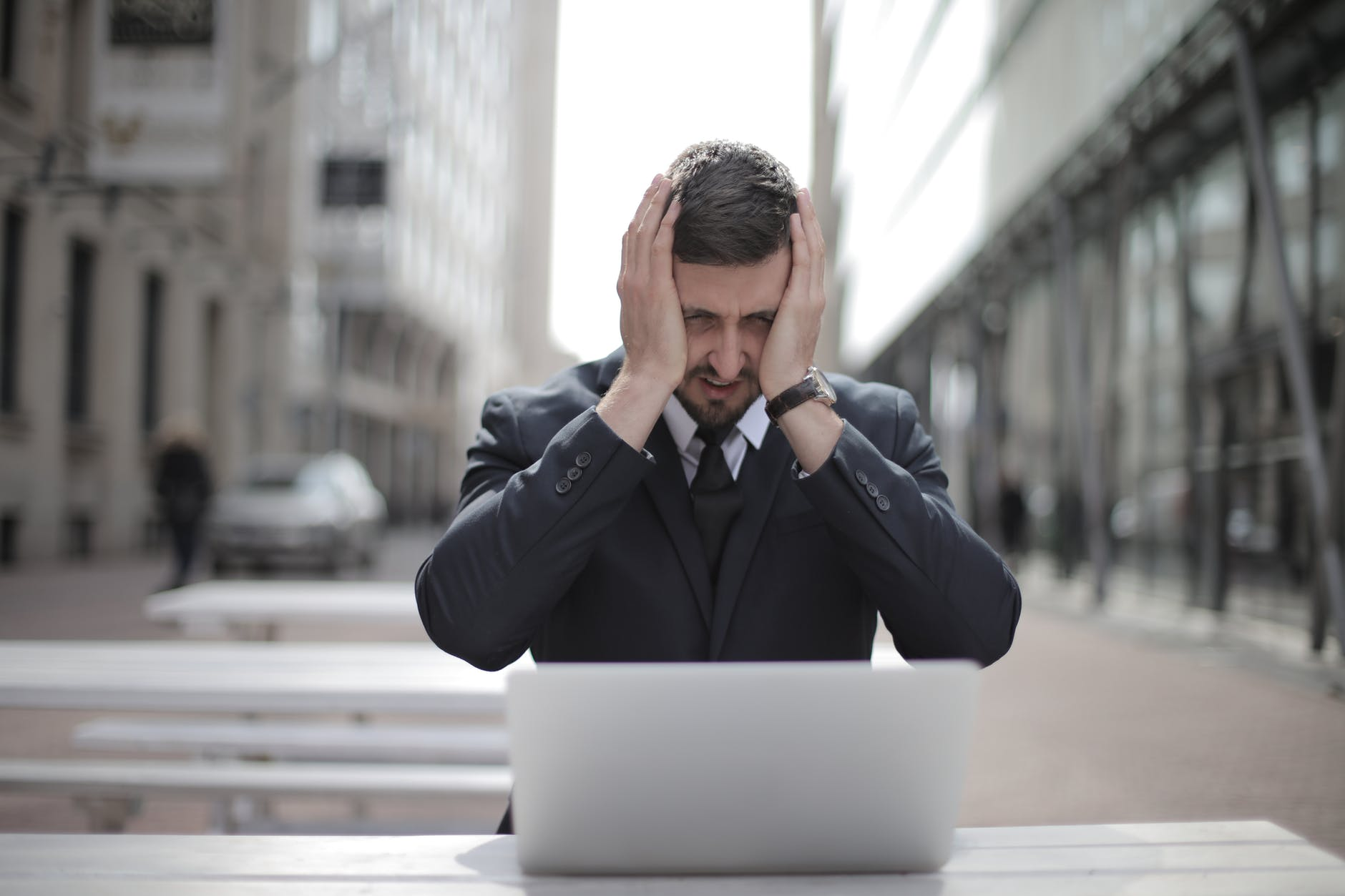 Stressed man in a suit in front of his laptop   Source: Pexels