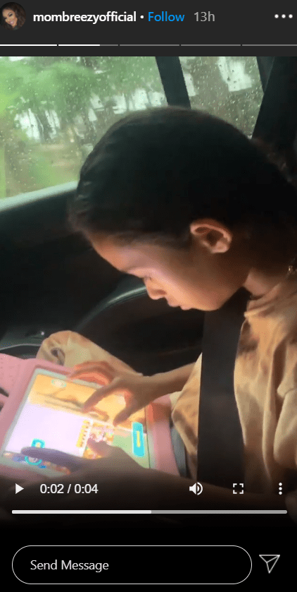 A picture of Royalty sitting in a car and using her tab. | Photo: Instagram/Mombreezyofficial