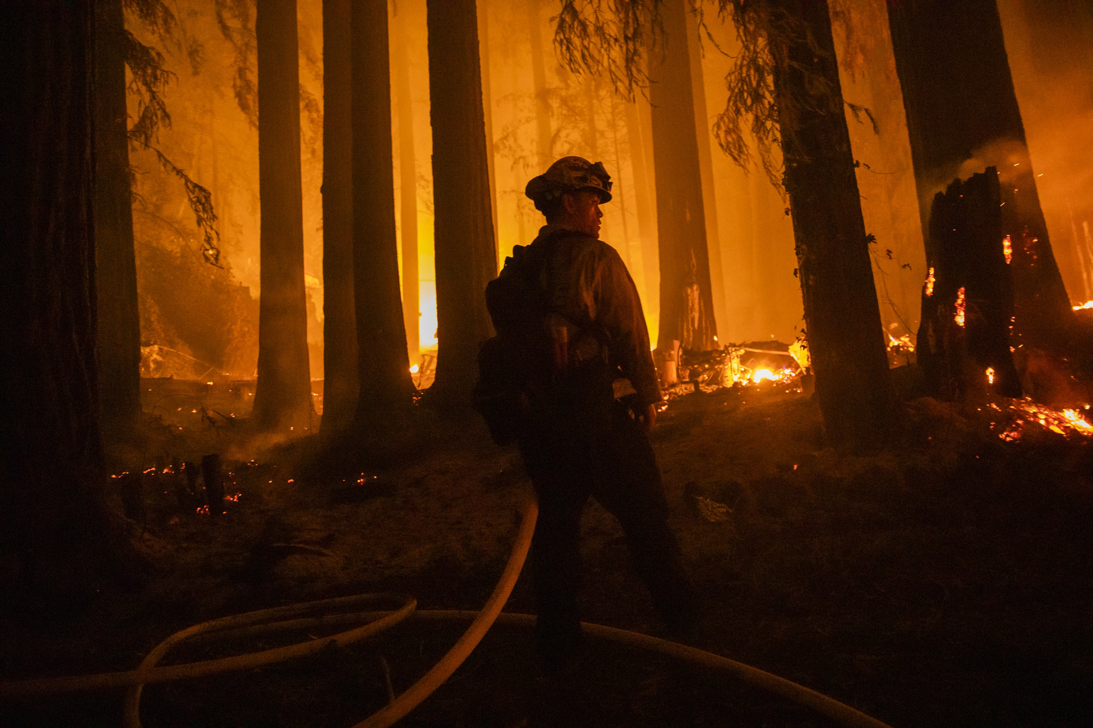 A firefighter with the Jameson Creek CDF station fights a fire on a property on Acorn Drive during the CZU Lightning Complex fire in Santa Cruz County, California, U.S., on Thursday, Aug. 20, 2020. | Source: Getty Images.