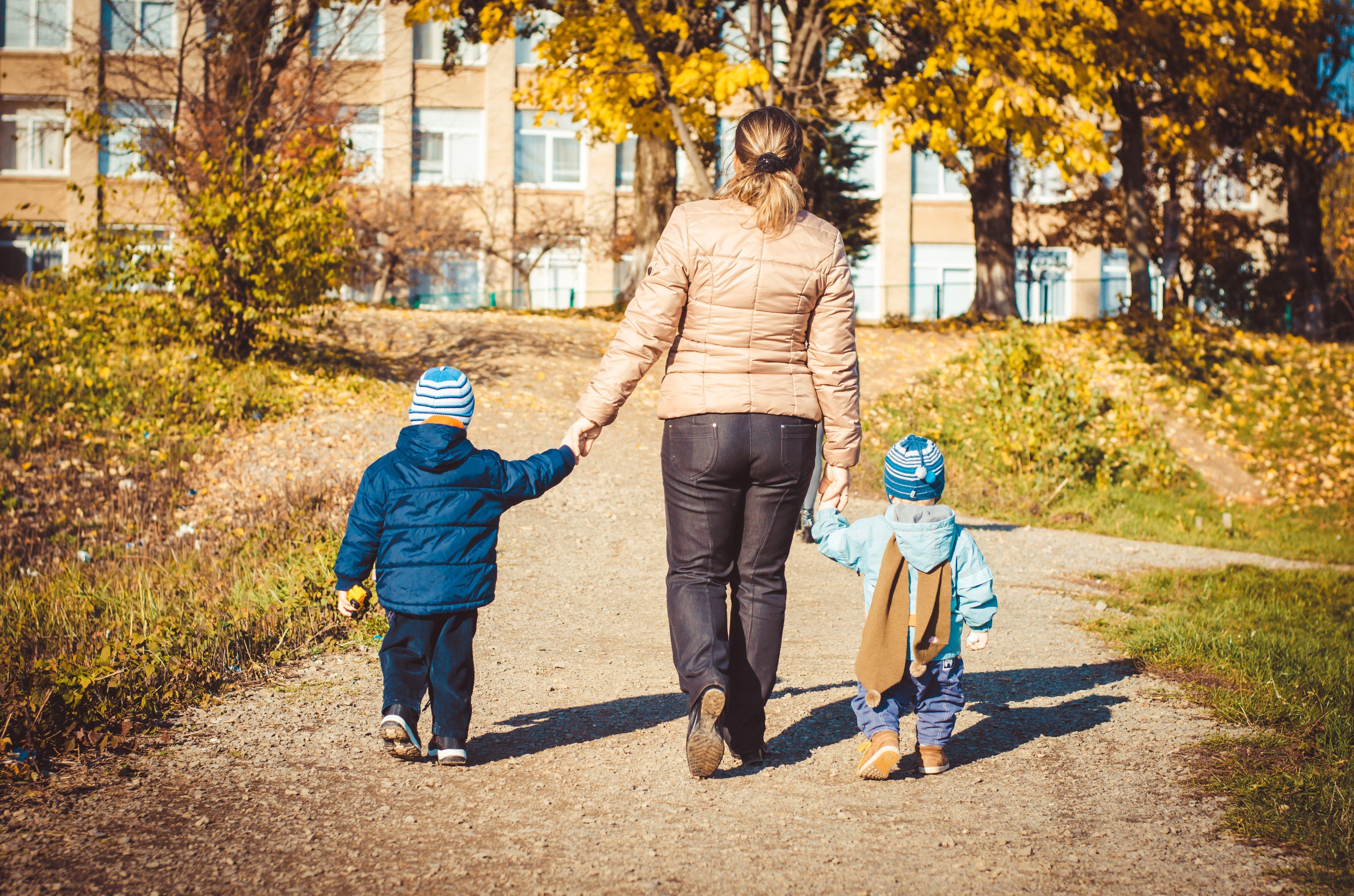 Vue arrière d'une mère et de deux filles marchant ensemble en se tenant la main | Photo : Shutterstock