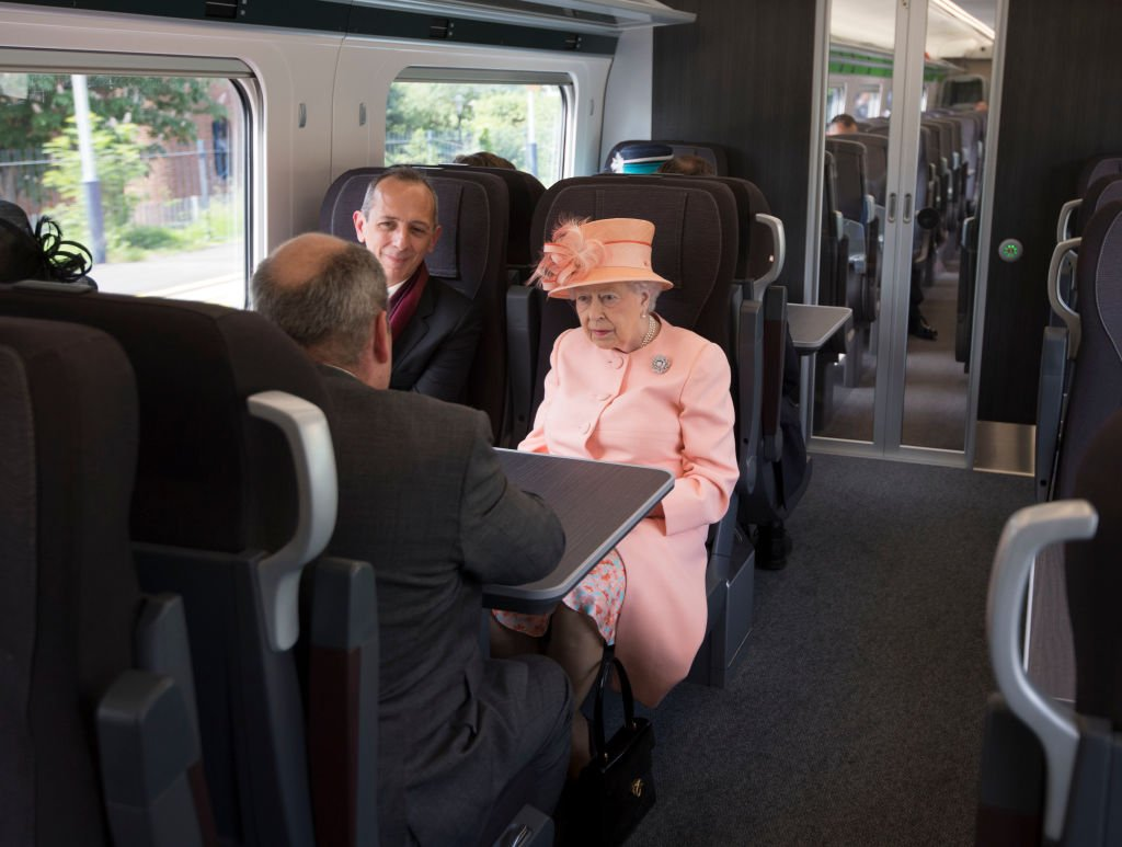 Queen Elizabeth II sits next to Isambard Thomas as she travels by train between Slough train station to Paddington Station on June 13, 2017, in London   Source: Getty Images