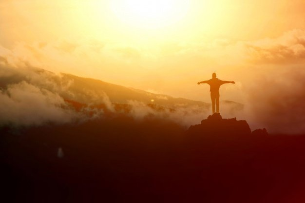 The silhouette of a man on top of a mountain. | Source: Freepik