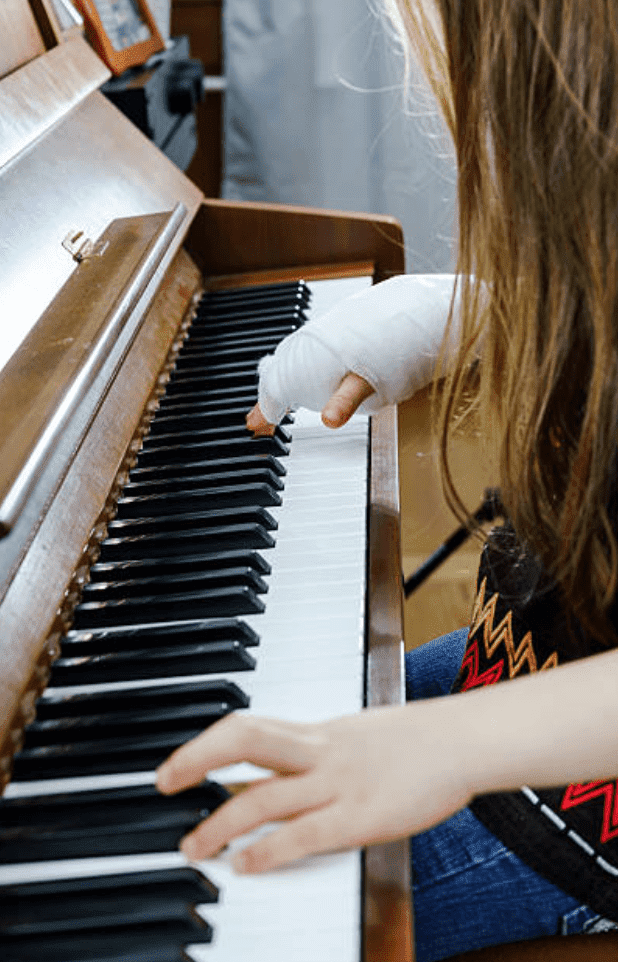 Child plays piano with bandaged hand | Source: Getty Images
