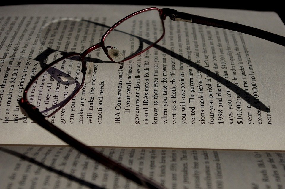 A pair of reading glasses and a book.   Photo: Pixabay