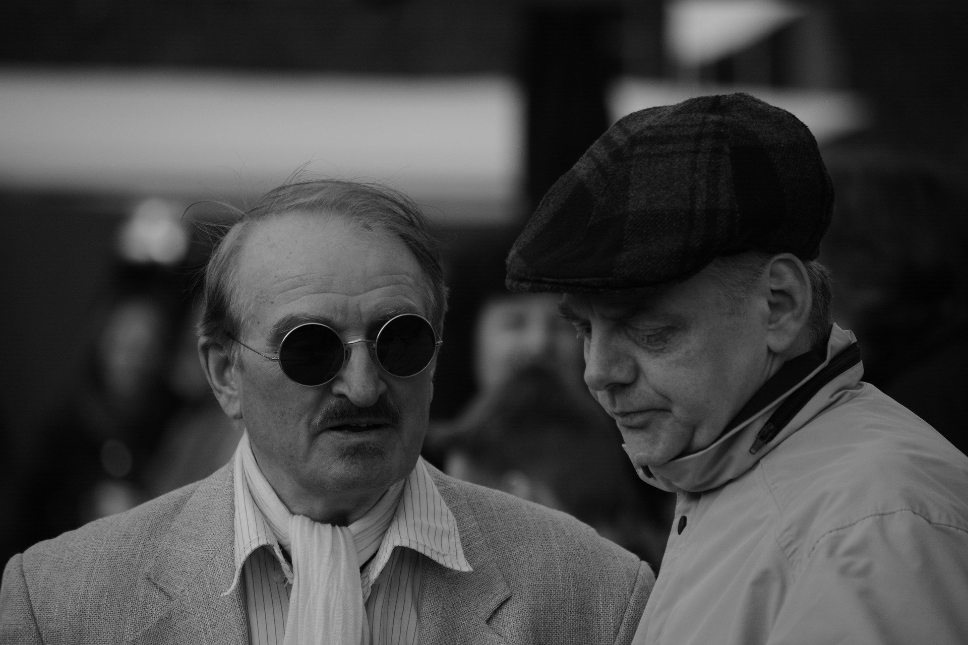 A black-and-white image of two men talking with one facing down   Photo: Pixabay/fsHH