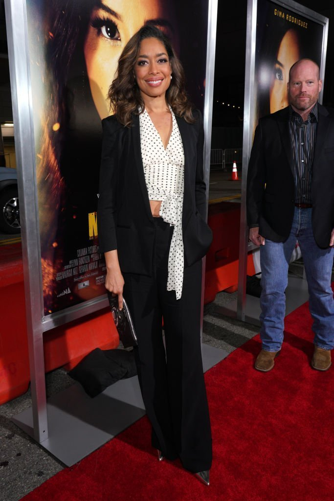 "Gina Torres posing at the ""Mama Bala"" premiere with Kevin White on the sidelines. 
