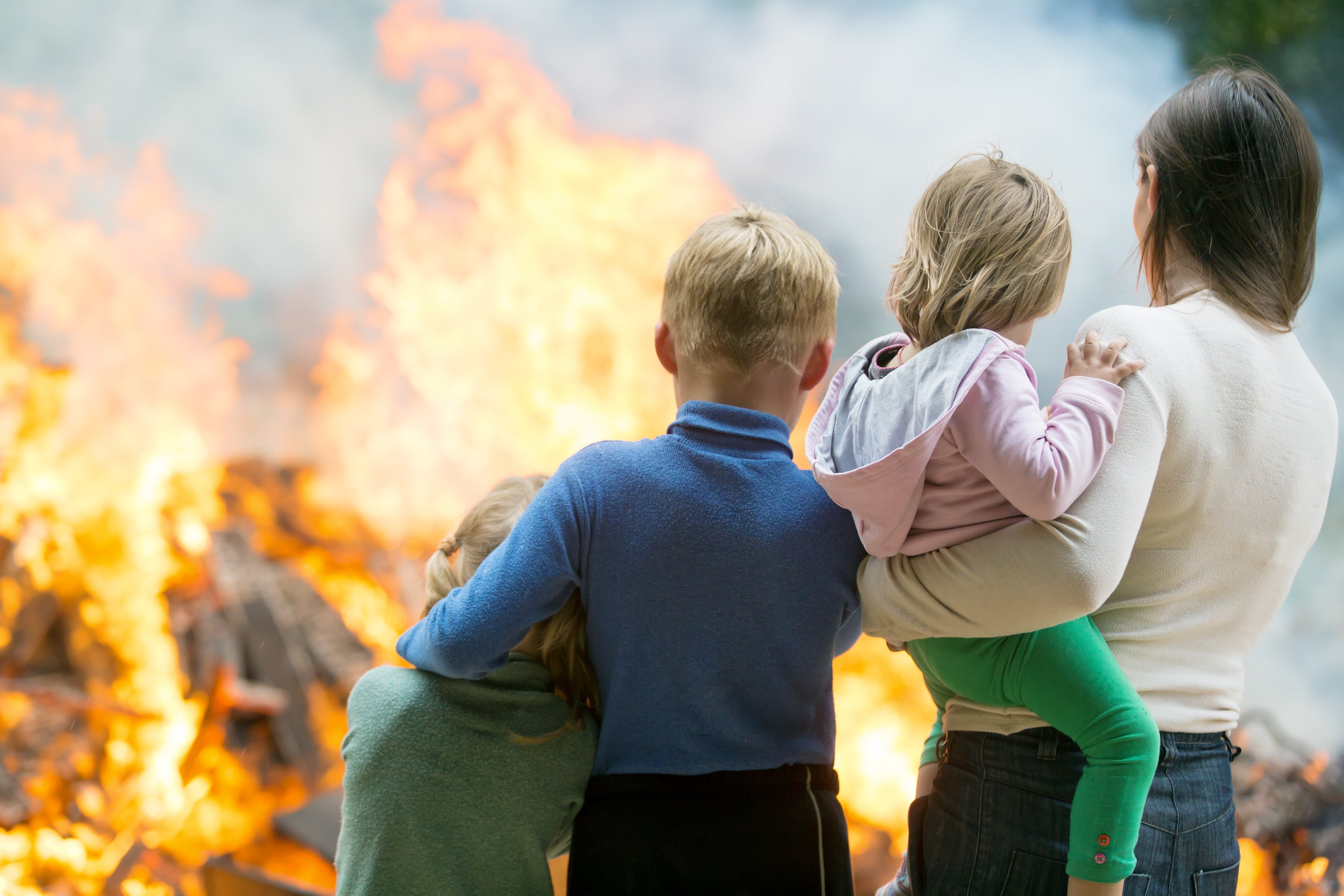 Family standing outside burning home. Image credit: Shutterstock