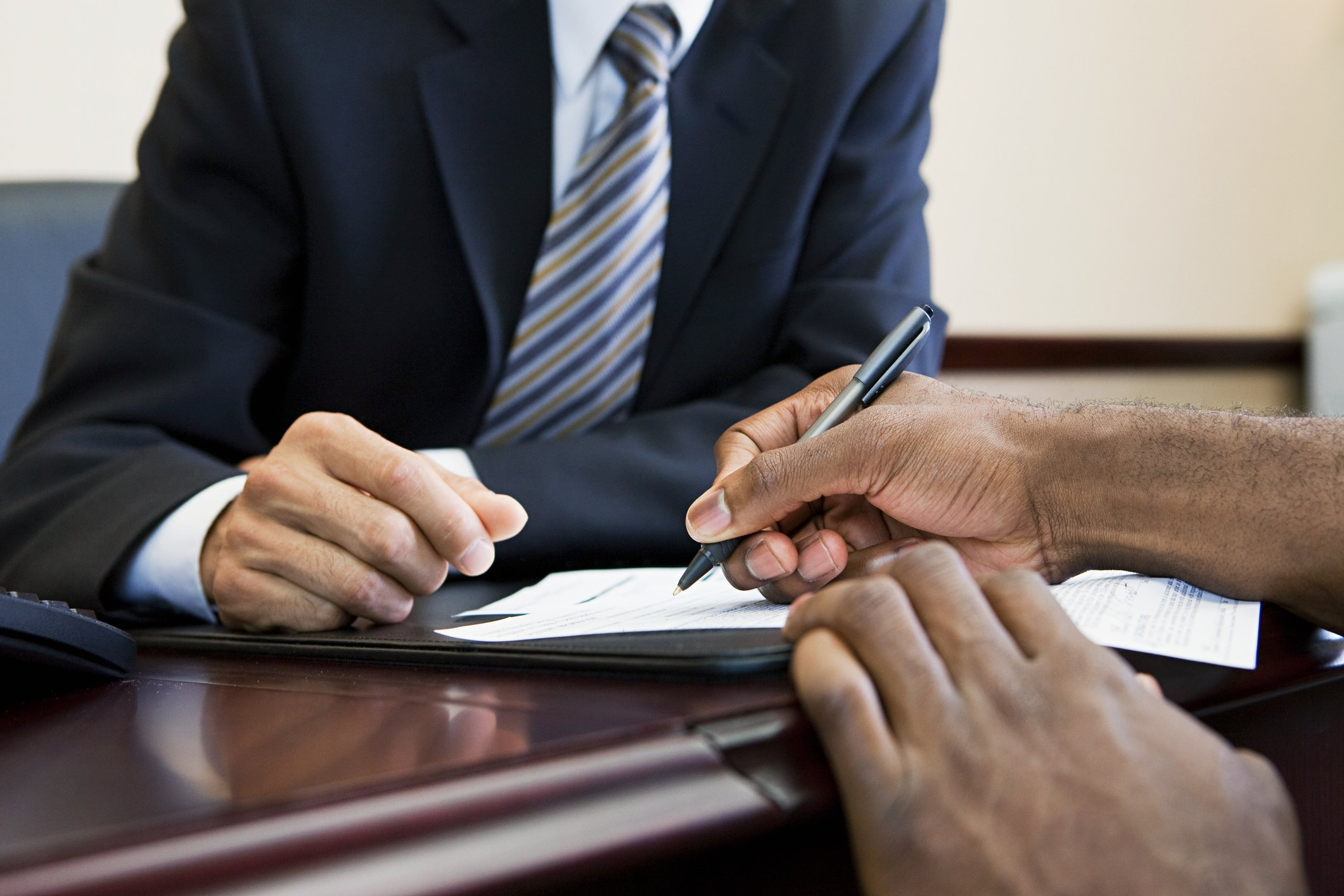 Customer signing paperwork with bank manager | Photo: Getty Images