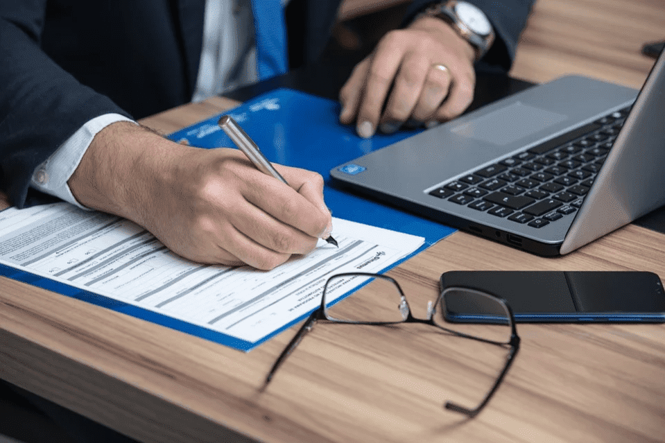 Man signing papers in an office | Photo: Pixabay