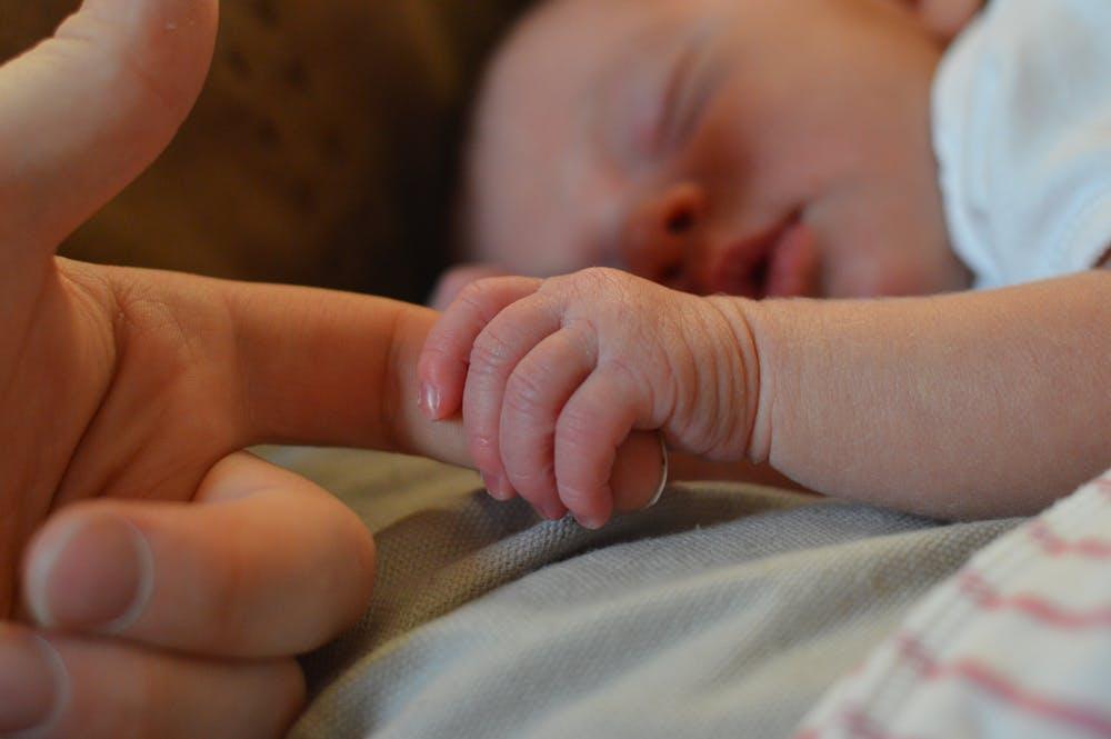 Bébé tenant le doigt de sa mère | Photo : Pexels
