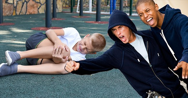 A boy looks injured while other kids laugh at him. | Source: Shutterstock