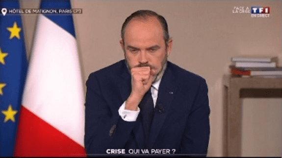 Le Premier ministre Edouard Philippe tousse sur sa main en direct de TF1 | Photo : TF1.