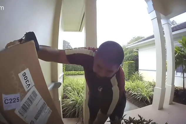 The USPS delivery worker stacking the FedEx packages in the corner | Photo: Youtube.com/Gabe White