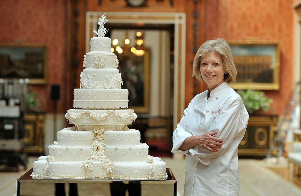 Fiona Cairns stands close to Prince William and Kate Middleton's Royal Wedding cake at the Buckingham Palace in London on April, 29, 2011. | Photo: Getty Images