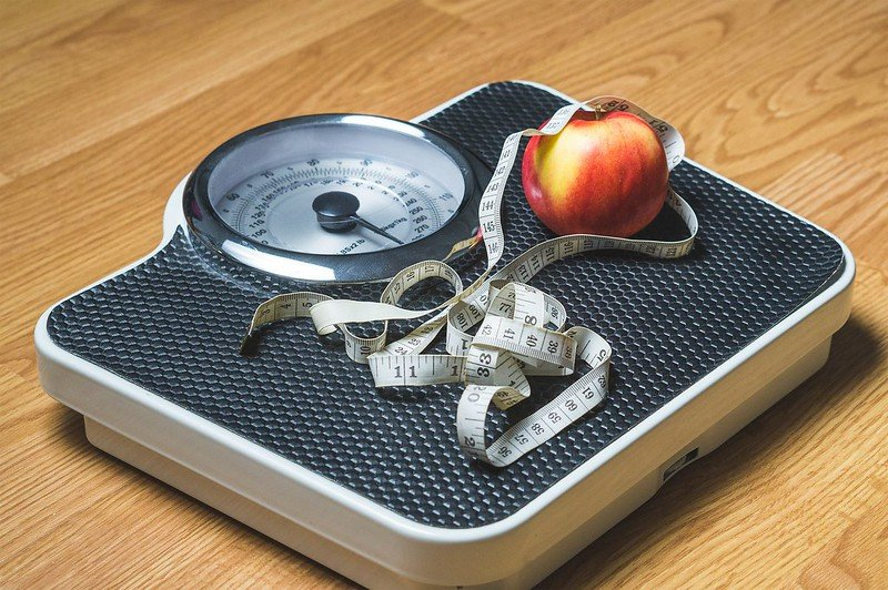 A weighing scale with an apple and a tape rule on it.   Photo:Flickr