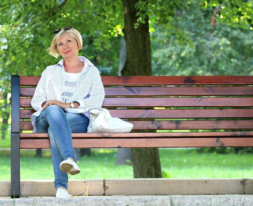 Mujer sentada en un banquillo mientras está pensativa en un parque. | Imagen: Pixabay
