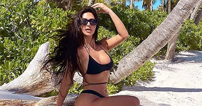 Kim Kardashian Flaunts Her Physique in a Black Swimsuit in a New Beach Photo