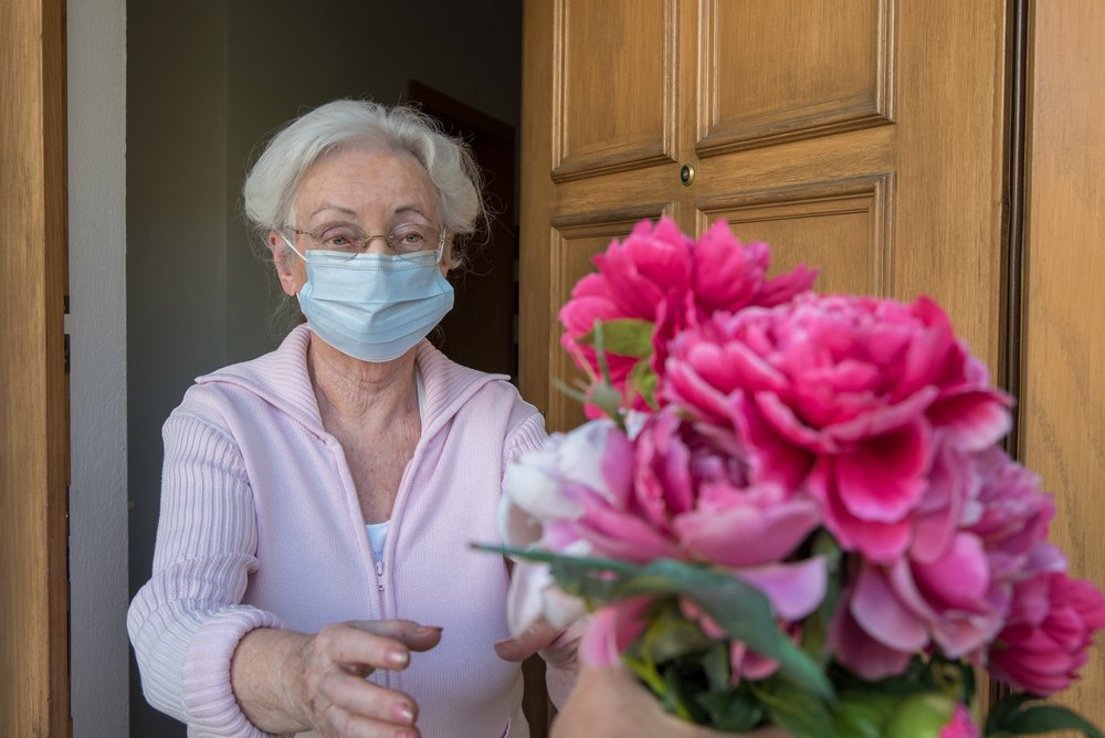 A senior woman wearinga protective face mask receivesflowers at her door on Mother's day | Photo: Shutterstock/Gulliver20